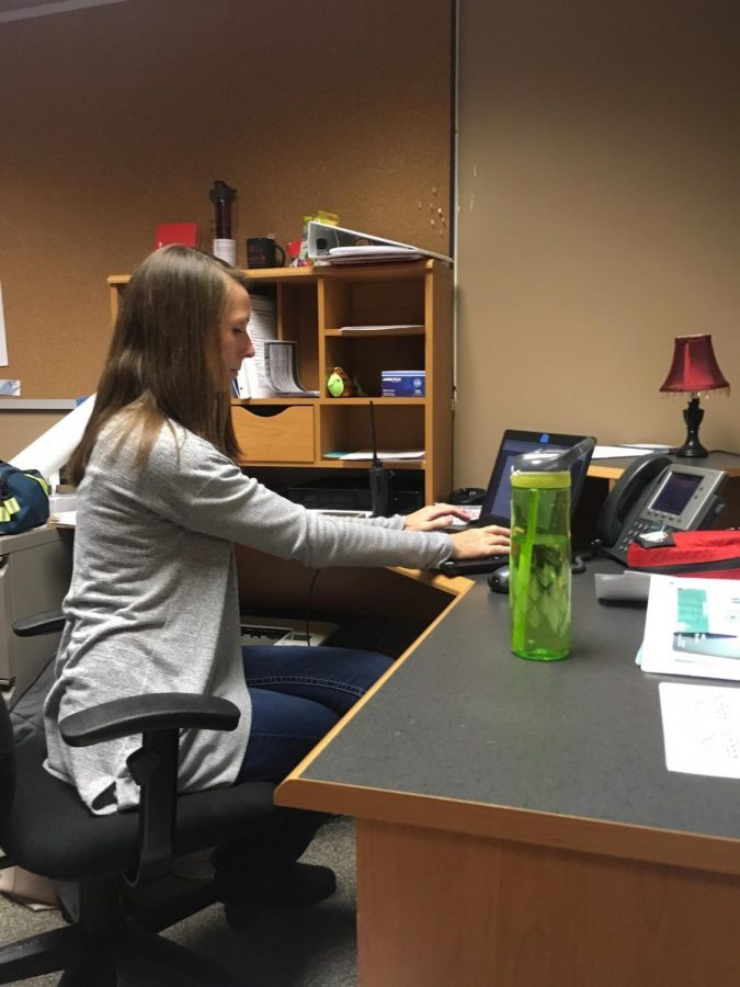 Amy Doolittle takes care of business, such as scheduling student conferences and answering questions from concerned parents, in her office.