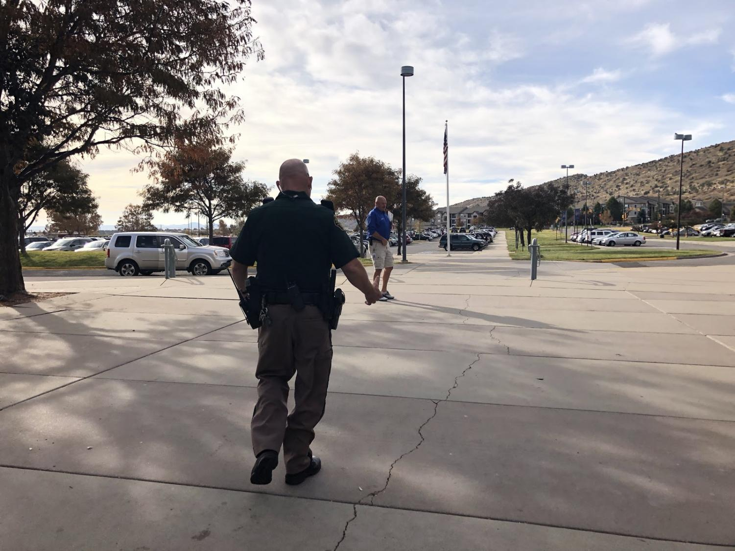 Dave Bruening, SRO officer at Dakota, meeting with another security member outside of Dakota Ridge High School. Both men were relaxed when speaking with fellow coworkers, calmly taking care of the situation at hand.