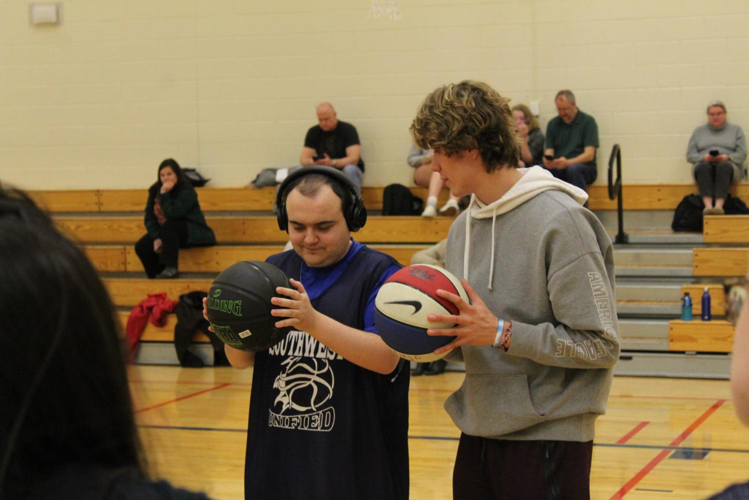 Photo Credits: Ryan Osborne  Junior Luke Loehding teaches a Unified Basketball player the to pass a basketball