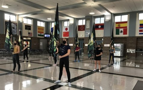The color guard team practices flag in the Dakota Ridge cafeteria, working hard to perfect their routines while maintaining social distance.