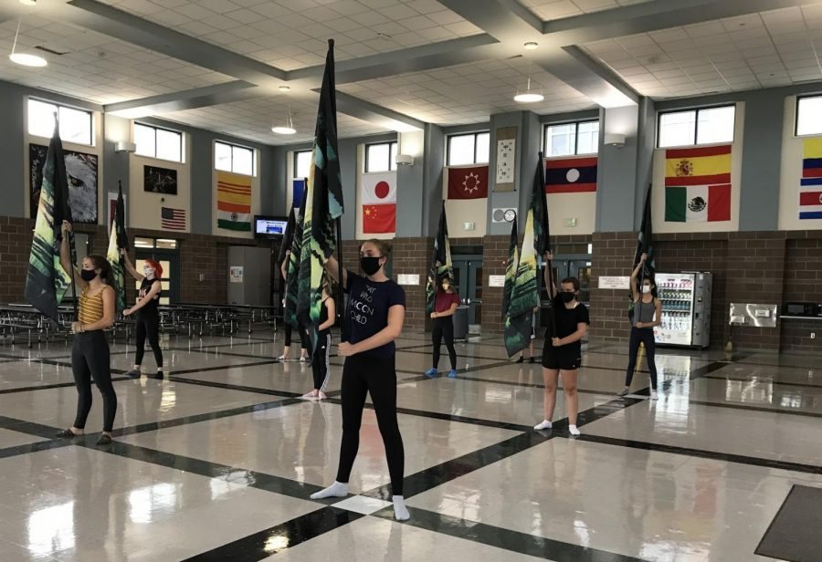 The+color+guard+team+practices+flag+in+the+Dakota+Ridge+cafeteria%2C+working+hard+to+perfect+their+routines+while+maintaining+social+distance.++