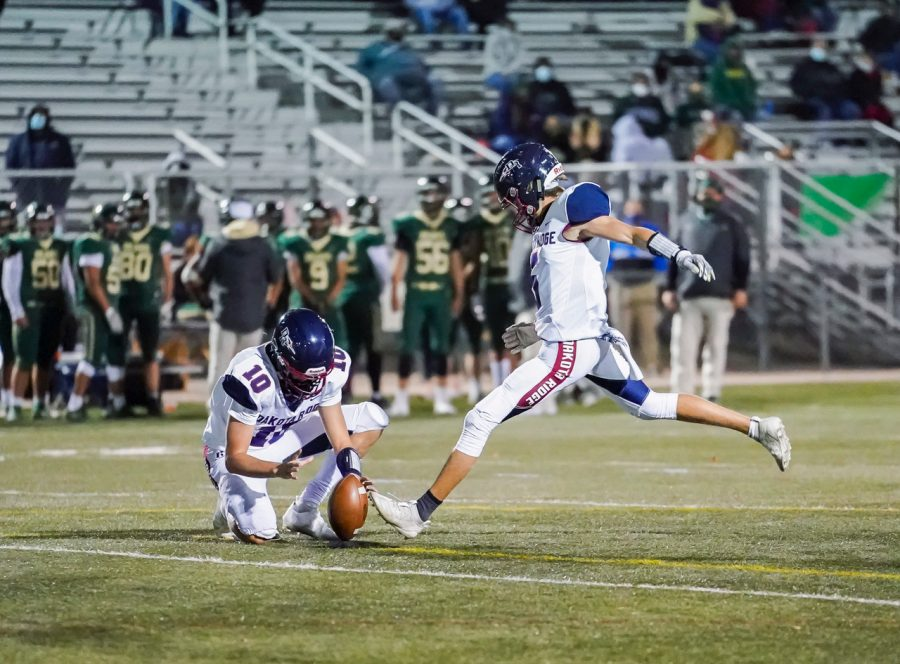 Dakota senior wide receiver/kicker Max Hart aims to kick the ball held by senior wide receiver Mason Galbreath, pursuing the field goal that will aid the team in their victory.