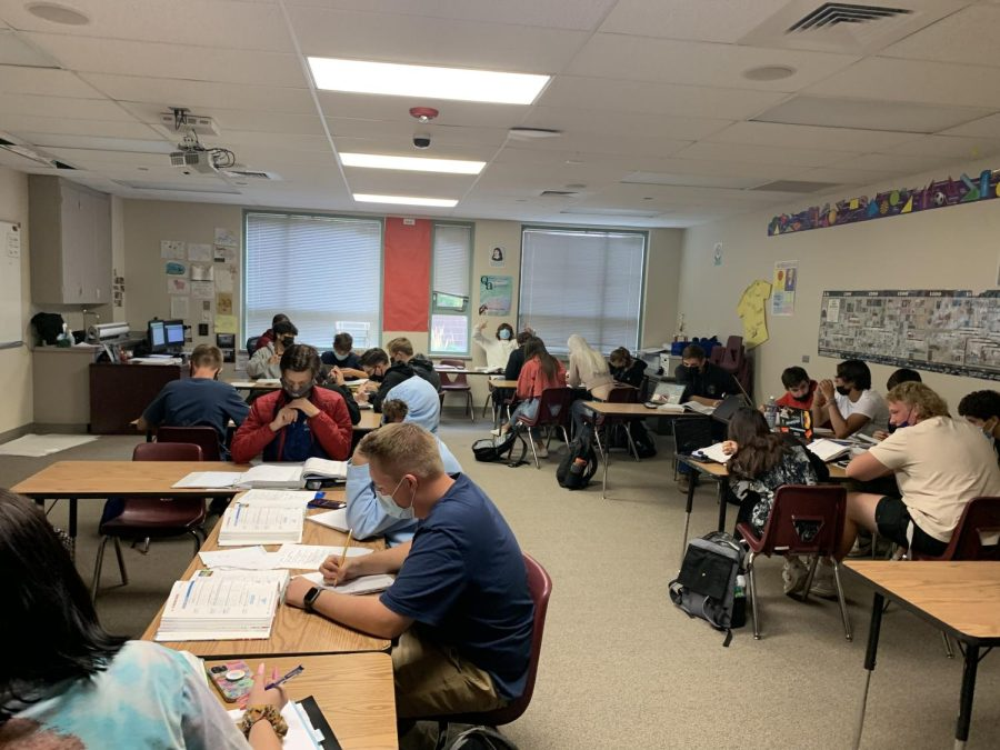 Jeremiah Behrendsen's Algebra 2 class. As the class works, students chat with their neighbors, and laughter fills the room, along with the sound of pencils scraping at the paper.